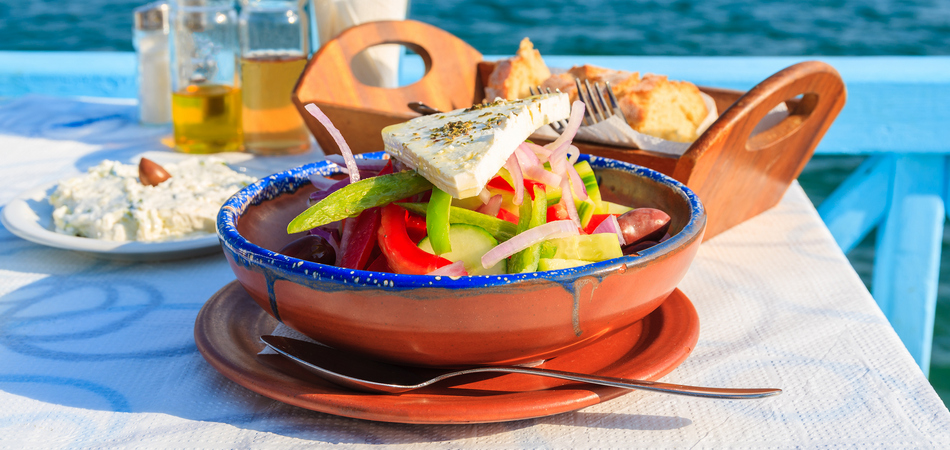 ORSH_Greek salad on table in Greek tavern with blue sea water in background, Samos island, Greece_800x600