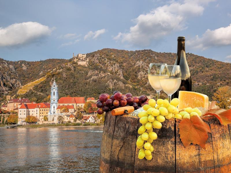 ORSH_Bottle of wine on barrel with Durnstein village in Wachau, Austria_800x600