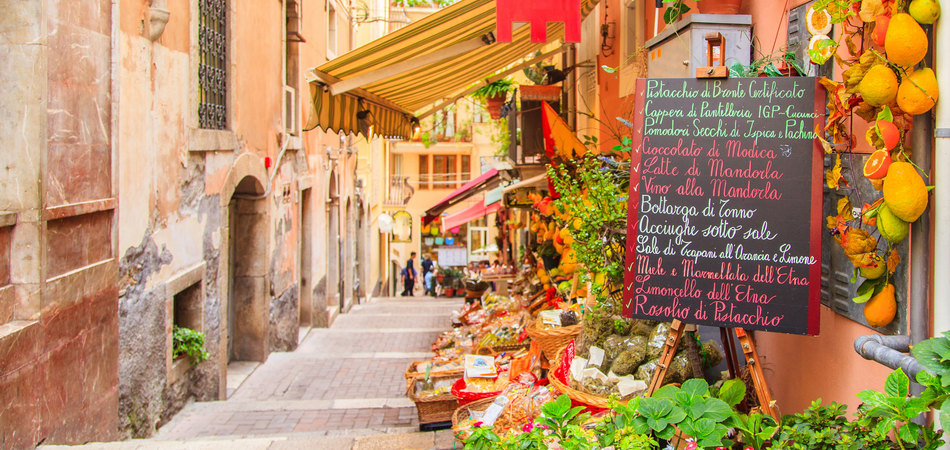 ORSH_Entrance to local shop in Taormina, Sicily. Writing on the black table lists itmes on promotion_950x450