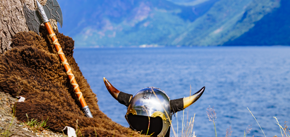 ORSH_Viking helmet with axe on fjord shore in Norway. Tourism and traveling concept_950x450