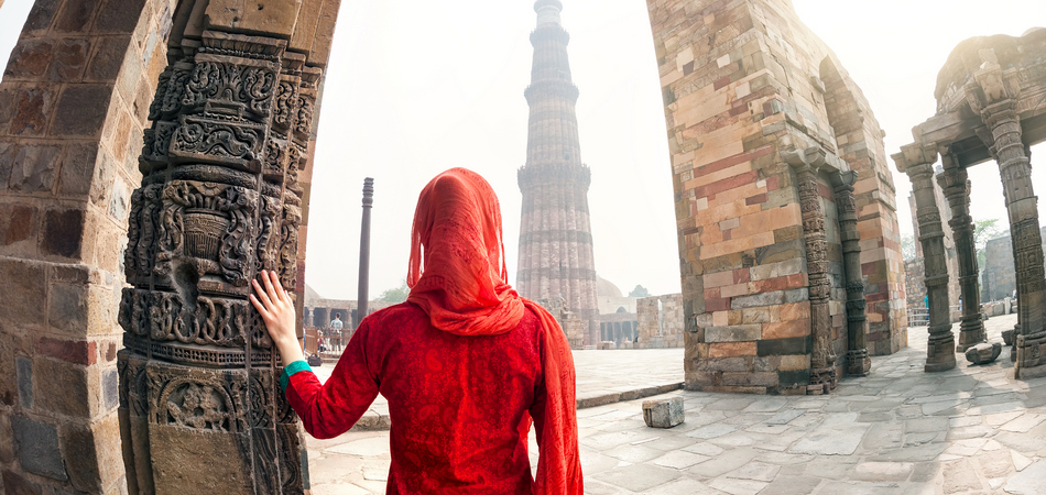ORSH_Woman in red costume looking at Qutub Minar tower in Delhi, India_950x450