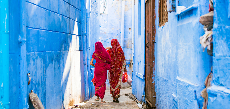 ORSH_Two women dressed in the traditional Indian Saree are walking through the narrow streets of the blue city of Jodhpur, Rajasthan, India._950x450