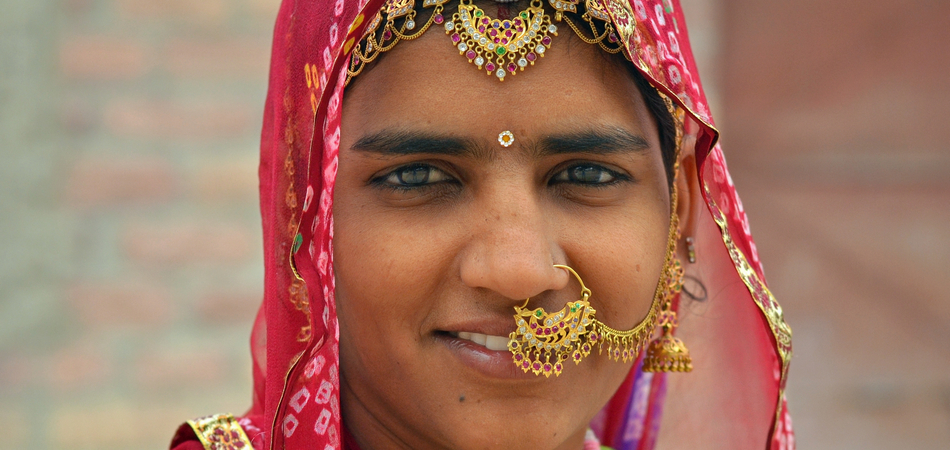 ORSH_oung Indian Bishnoi woman with headscarf (dupatta) wears elaborate nose and forehead jewelry and poses for the camera, on Feb 28, 2015._950x450
