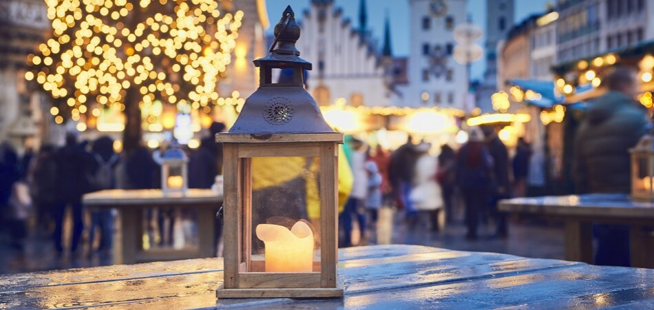 Traditional christmas market in city. Selective focus on lantern with burning candle. Marienplatz in Munich, Germany.