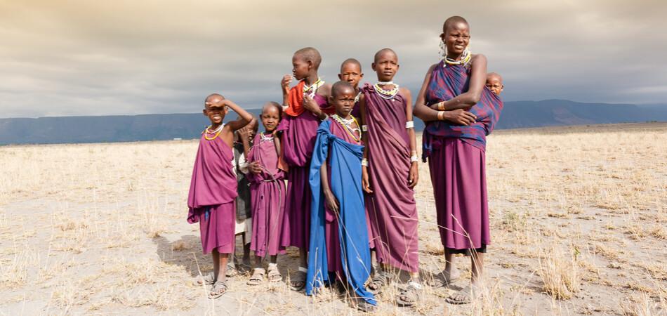 950x450 ORSH_Masai woman and a children in the African savannah, looking at camera.Tanzania