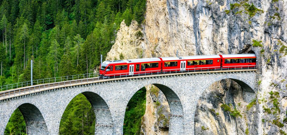 Landwasser Viaduct in Filisur, Switzerland. It is a famous landmark of Swiss Alps. Red express train runs from mountain tunnel on high bridge. Scenic aerial view of amazing railway in summer.