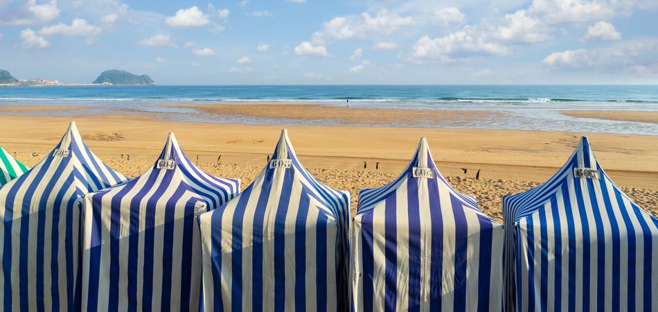 colorful blue and white tents of Zarauz beach, Pais Vasco, Spain
